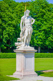 Nymphenburg, Germany - July 30, 2015: Neptun sculpture, king of the seas, beautiful sunny day, green grass and bushes in Royalty Free Stock Photography