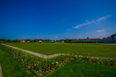 Nymphenburg, Germany - July 30, 2015: Very big grass field bathing with sunshine, some buildings in background, palace. Gardens stock images