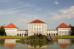 Nymphenburg palace in Munich. Nymphenburg palace and garden lake with fountain at sunset - located in Munich, Bavaria, Germany Royalty Free Stock Photography