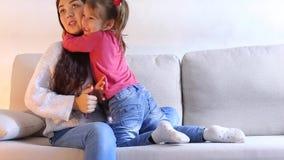 NYoung母亲坐长沙发和给小女儿phonen 影视素材