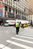 NYPD交通官员指挥步行者和交通的在第六条大道交叉路和西部第35条街道,曼哈顿 库存照片