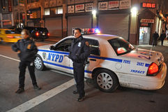 NYPD. Police officers standing in front of their car, night scene in New York City Stock Photography
