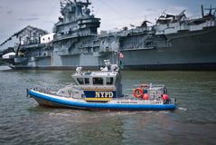 NYPD Boat and Intrepid Carrier Royalty Free Stock Photos