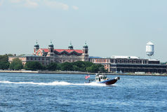 NYPD boat patrolling New York Harbor in the front of Ellis Island Royalty Free Stock Photo