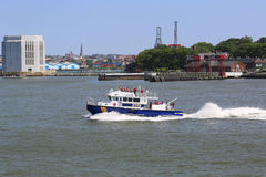 NYPD boat patrolling New York Harbor in the front of Governors Island Royalty Free Stock Images