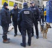 NYPD-Terrorismusbekämpfungsoffiziere und NYPD fahren Polizeibeamten des Büros K-9 mit dem Hund K-9 durch, der Sicherheit auf Broad Lizenzfreie Stockfotos