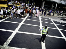 NYPD Traffic cop. An NYPD traffic cop wearing a reflective vest directs traffic at a crossing Stock Photography