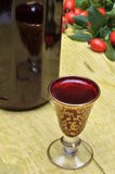 Nyponfrukt och alkoholiststarksprit i en flaska och ett exponeringsglas Royaltyfri Bild