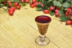 Nyponfrukt och alkoholiststarksprit i ett exponeringsglas Arkivfoto