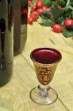 Nyponfrukt och alkoholiststarksprit i flaskor och exponeringsglas Arkivbilder
