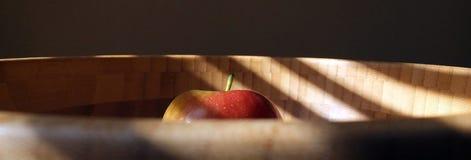 Nytt äpple i bambubunke under naturligt ljus arkivfoton