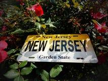 Nytt - ärmlös tröja, den Garden state registreringsskylten som lägger i en trädgård av blommor arkivfoto