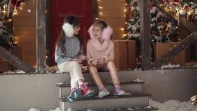 Nytt år eller jul barn sitter på farstubron mot bakgrunden av trädet för det nya året och talar arkivfilmer