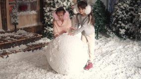 nytt år för jul Barn gör en snögubbe två små flickor gör en boll av snö stock video