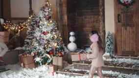 nytt år för jul barn ger sig gåvor för jul på trädet för det nya året lilla flickan bär a lager videofilmer