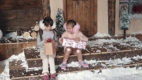 nytt år för jul barnutbytesgåvor för jul två små flickor på bakgrunden av `en s för nytt år lager videofilmer