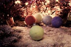 Nytt år för tappning, julbakgrund med mång- färgjulpynt på snö Fotografering för Bildbyråer