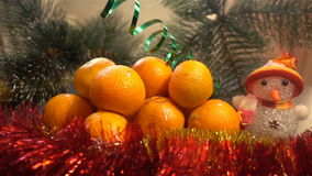 nytt år Julsammansättning av mandariner, julgranfilialer och en snögubbe arkivfilmer