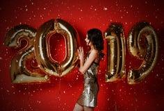 nytt år Kvinna med ballonger som firar på partiet Stående av den härliga le flickan i skinande guld- klänning som kastar konfetti royaltyfri foto