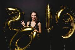 nytt år Kvinna med ballonger som firar på partiet Stående av den härliga le flickan i skinande klänning som kastar konfettier arkivbilder