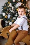 nytt år Pojke som spelar nära julgranen arkivfoton