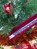 Nytt års bollar på filialer av en julgran och en halsbandgåva. Stilleben Royaltyfri Fotografi