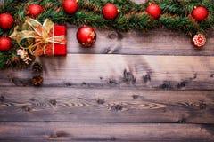 Nytt års dekor och festliga leksaker på en trätabell med en röd radask med en gåva Santa Claus royaltyfri bild