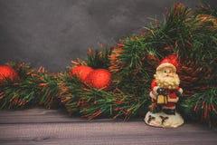 Nytt års dekor och festliga leksaker på en trätabell med en röd radask med en gåva Santa Claus lyckligt nytt år royaltyfri fotografi
