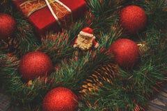 Nytt års dekor och festliga leksaker på en trätabell med en röd radask med en gåva Santa Claus lyckligt nytt år arkivbild