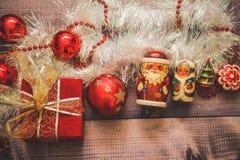 Nytt års dekor och festliga leksaker på en trätabell med en röd radask med en gåva Santa Claus och en nötknäppare lycklig ny yea royaltyfri fotografi