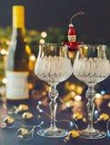 Nytt års garneringar med vinglas, julgranen och klockan royaltyfri fotografi