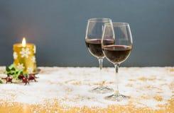 Nytt års helgdagsaftonjubel med två exponeringsglas av rött vin och druvor Arkivbild
