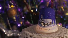 Nytt års lampa med en stearinljus på bakgrunden av en dekorerad julgran med en glödande girland arkivfilmer