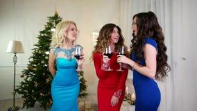 Nytt års parti per gruppen av flickor nära julgranen, drinkalkohol från av vinexponeringsglas, ursnygga unga kvinnor stock video