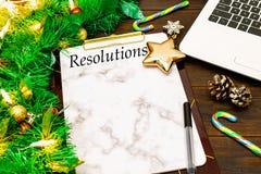 2019 nytt års upplösningar och bärbar dator med julträdfilialer, guld- stjärna, godisrotting, kottar på träbakgrund arkivfoto