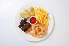 Nytt ölmellanmålsortiment på en vit platta Pommes frites, krutonger och zucchini och söt peppar arkivbilder