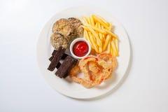 Nytt ölmellanmålsortiment på en vit platta Pommes frites, krutonger och zucchini och söt peppar arkivfoto