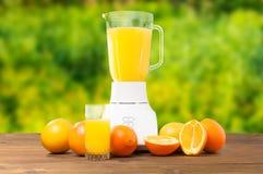 Nytt apelsin och exponeringsglas av orange fruktsaft på trätabellen Royaltyfria Foton