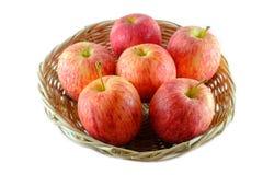 Nytt av äpplet på en korg som isoleras på vit bakgrund Arkivbild