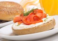 Nytt bakad bagel med gräddost, lox och orange fruktsaft Royaltyfri Bild