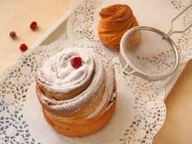 Nytt bakad cruffin som dekoreras med sockerpulver och torkade tranbär Slut upp, bästa sikt arkivfoto