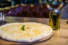 Nytt bakad focacciapizza med parmesanost på en träställning på en trätabell med en flaska av olivolja Royaltyfri Bild