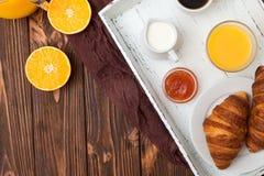 Nytt bakad giffel, orange fruktsaft, nya frukter, driftstopp på brun träbakgrund Franskan frukosterar nya bakelser för morgon Arkivbild