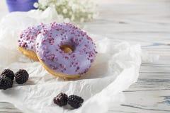 Nytt bakade björnbärdonuts med morgonfrukostinställningen royaltyfria foton