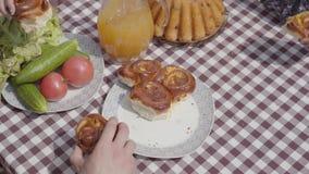 Nytt bakade kakor som ligger på tabellen nära grönsaker och fruktsaftkruset Händer av modern, fadern och att ta för barn stock video