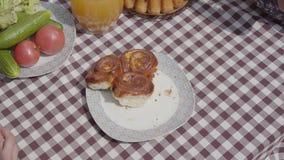 Nytt bakade kakor som ligger på tabellen nära grönsaker och fruktsaftkruset Händer av oigenkännligt folk som tar stycken av lager videofilmer