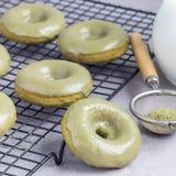 Nytt bakade matchabanandonuts med citrus glasyr för matcha på att kyla kuggen, fyrkantigt format Royaltyfria Bilder