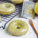 Nytt bakade matchabanandonuts med citrus glasyr för matcha, på att kyla kuggen och trätabellen, fyrkantformat Royaltyfri Fotografi