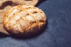 Nytt bakade runda hemlagade bröd på svart bakgrund Royaltyfria Bilder