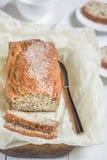 Nytt bakat bröd med sesamfrö på ett träbräde på en lig Royaltyfria Foton